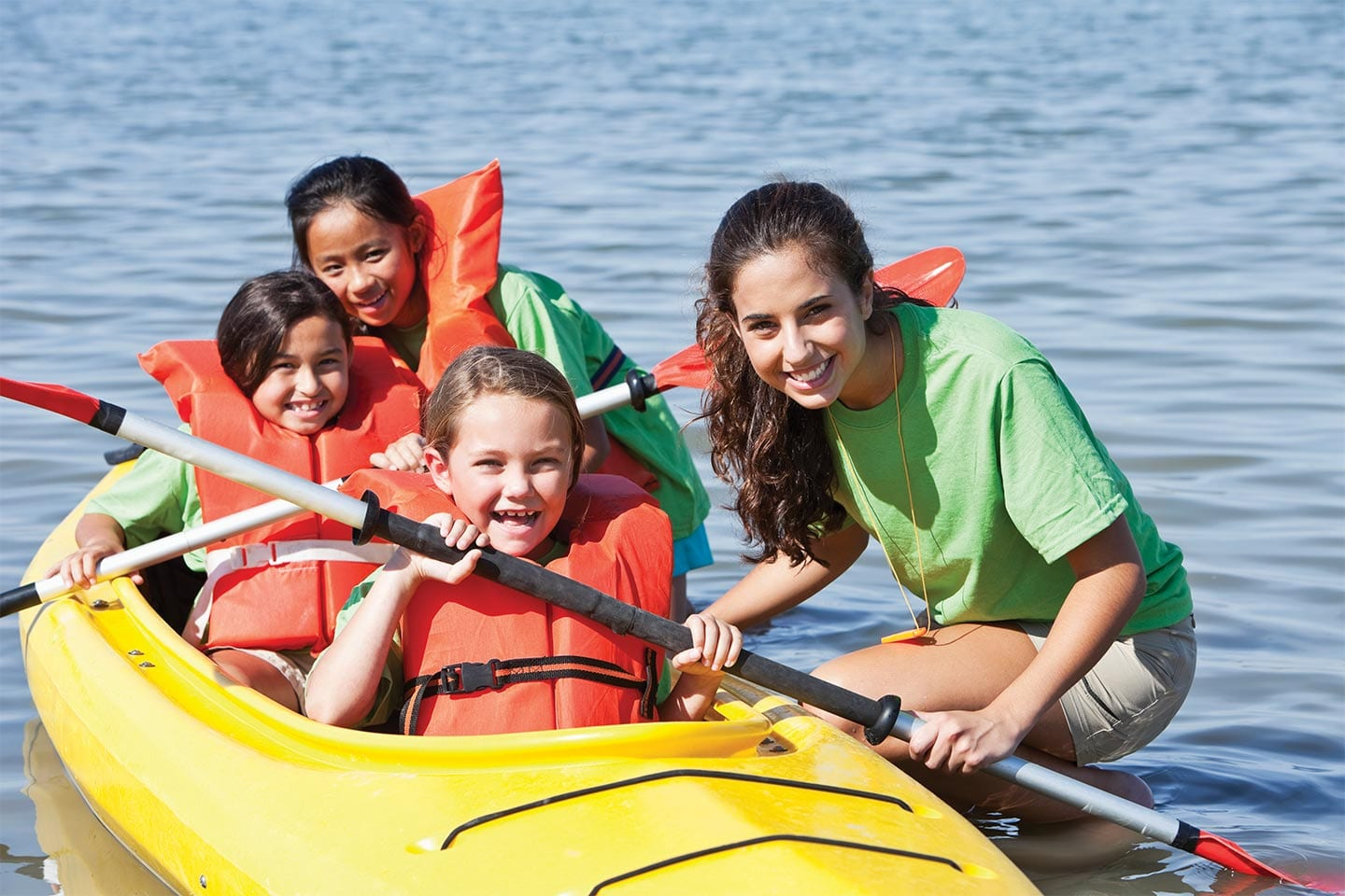 Kids in kayak with camp counselor